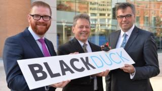Economy Minister Simon Hamilton, President and CEO of Black Duck Software Lou Shipley and CEO of Invest NI, Alastair Hamilton.