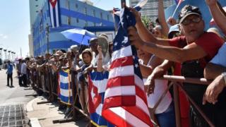 Cubans hold US and Cuban flags outside the US embassy building as the US flag is raised over it in Havana on August 14, 2015, during US Secretary of State John Kerry's visit