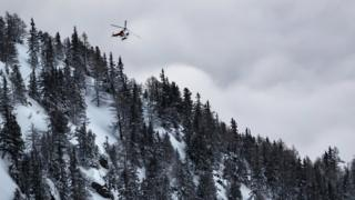 A rescue helicopter leaves the location of an avalanche after two people were swept away in Switzerland, 18 February 2018