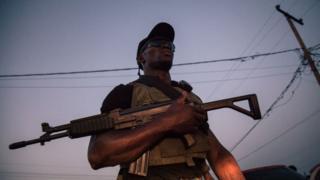 Soldier wey hold gun.