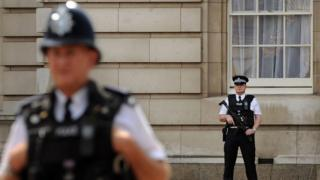 Stock image of police officers in front of Buckingham Palace
