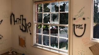 Smashed windows and graffiti on interior walls