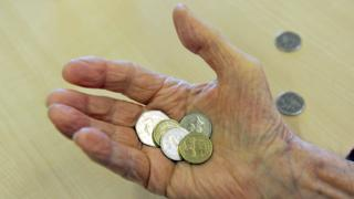 Elderly person with a handful of coins