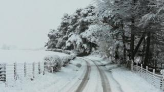 Snowy road and field at Hartside, Northumberland