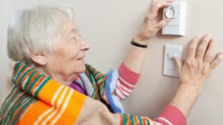 elderly woman adjusts thermostat
