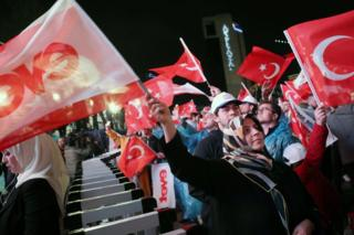 Supporters of Turkey's president celebrate as they wave Turkish national flags during a rally near the headquarters of the ruling AP in Ankara, 16 April