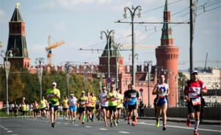 Runners race past the Kremlin during the Moscow Marathon