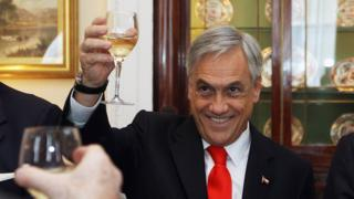 Mr Pinera raises a glass of wine during a trip to London in late 2010