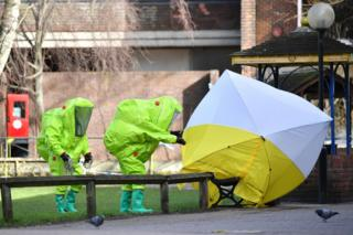 Members of the emergency services in green biohazard encapsulated suits fix the tent a bench