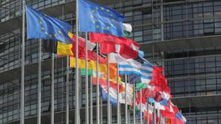 Flags of the European Union fly outside the European Parliament