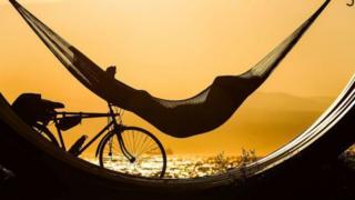 Pessoa deitada em rede aproveitando tempo livre