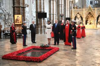 US President Donald Trump, accompanied by his wife Melania and Prince Andrew, Duke of York, places a wreath on the grave of the unknown warrior during a visit to Westminster Abbey