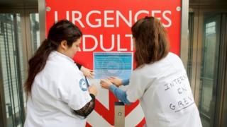 Student doctors on strike place a poster in front of a hospital during a strike to denounce the lack of resources, their working conditions and status in Marseille, France
