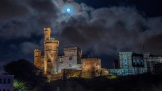 Inverness castle seen from below with the moon high above