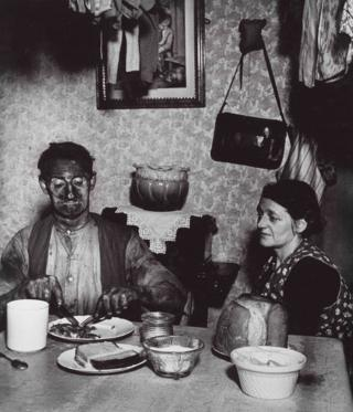 A photograph of a miner eating a meal at a dinner table as a woman looks on