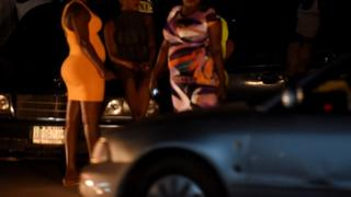 Three sex workers stand on the street in Benin City, capital of Edo State, southern Nigeria