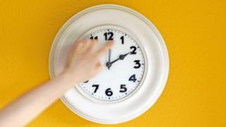 Mão de pessoa ajusta ponteiro em relógio