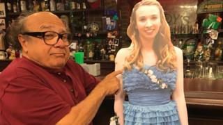 Danny DeVito stands next to a cardboard cutout of a teenager in a prom dress in Paddy's Pub, on the set of TV show It's Always Sunny in Philadelphia