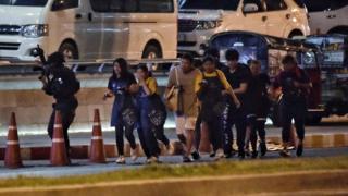 被挾持的民眾在軍警護送下離開槍擊現場。