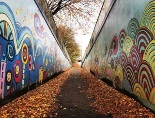 Street art and fallen leaves along a path