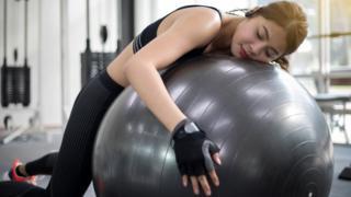 mulher dormindo enquanto faz exercício