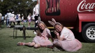 Two girls wearing rabbit ears sit during the annual Colour run on November 12, 2016 in Cape Town, South Africa.