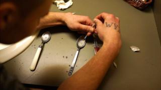Un hombre prepara una dosis de heroína para inyectársela.