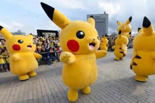 people in Pikachu costumes onstage in Japan