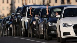 People in cars honk and show their hands with white ribbons - symbols of the protests - on their wrist
