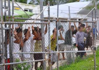 Asylum-seekers look through a fence at the Manus Island detention centre in Papua New Guinea 21 March 2014.