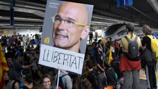 "Protesters hold a picture of deposed Catalan regional government""s foreign relations chief Raul Romeva reading ""Freedom"" as they block train tracks at the Sants Station in Barcelona during a strike called by a pro-independence union in Catalonia on November 8, 2017."