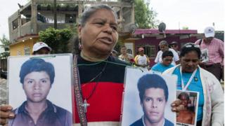 Clementina Murcia González holds up the pictures of her two sons