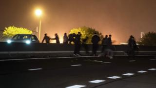 File pic of migrants crossing main road near Calais
