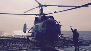 A helicopter waits to take off
