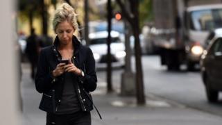 أحد المارة تُحدق في هاتف محمول أثناء السير