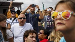 Visitors and tourists ride a ferry toward Liberty Island and the Statue of Liberty, August 8, 2017 in New York City.
