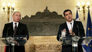 Alexis Tsipras and Vladimir Putin speaking from lecterns at a press conference