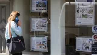 Woman looks in estate agent window