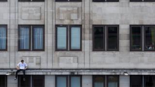 Pria duduk di pinggir apartemen di Waterloo, London, Inggris.