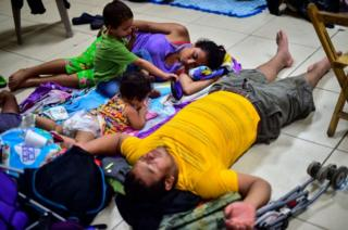 A man, a woman, and two small children rest at a temporary shelter in Ciudad Hidalgo, Mexico