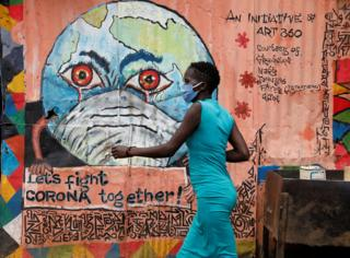A woman in a blue dress walks past a pink mural depicting planet Earth wearing a face mask and crying.
