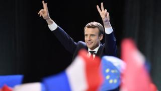 "Emmanuel Macron hold his hands up in a ""peace sign"" gesture with the French and EU flags visible in the foreground"