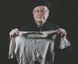 潘信行依旧保存着父亲受刑时所穿、被弹孔穿过的衣服。