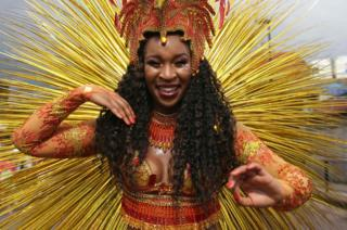 A performer in costume poses on the second day of the Notting Hill Carnival in west London