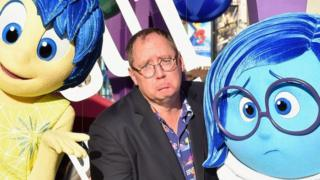 John Lasseter is pictured comically frowning, seated between the characters of Joy and Sadness from Pixar's Inside Out in 2015