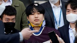 Cho Ju-bin outside the police station, wearing a neck brace