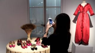 A visitor photographs some YSL shoes