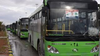 Buses which will be used to evacuate civilians leaving from rebel-held areas of Aleppo are seen waiting on 14 December 2016