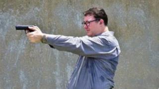 A screenshot of a Facebook post showing Australian MP George Christensen aiming a gun