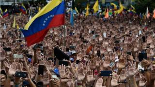 """People raise their hands during a mass opposition rally against President Nicolas Maduro in which Venezuela's National Assembly head Juan Guaido (out of frame) declared himself the country's """"acting president"""", on the anniversary of a 1958 uprising that overthrew a military dictatorship, in Caracas on January 23, 2019"""